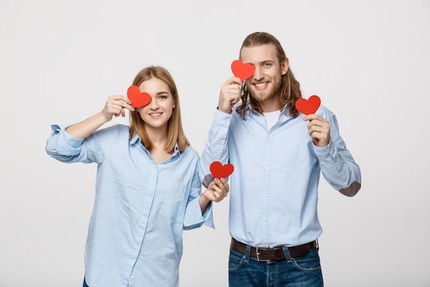 Séduisante jeune couple amoureux tenant des coeurs rouges sur les yeux sur fond blanc