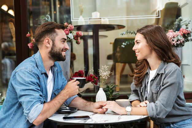 Séduisante jeune couple amoureux en train de déjeuner assis à la table du café à l'extérieur, buvant du café, parlant