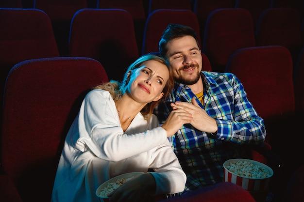 Séduisante jeune couple caucasien regardant un film dans un cinéma, une maison ou un cinéma. ayez l'air expressif, étonné et émotif. s'asseoir seul et s'amuser. relation, amour, famille, week-end.
