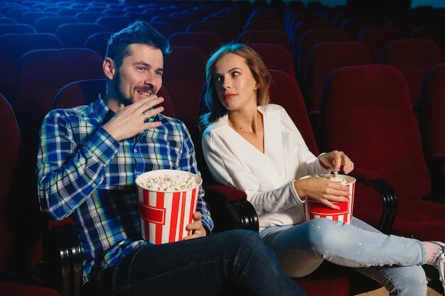 Séduisante jeune couple caucasien regardant un film dans un cinéma, une maison ou un cinéma.