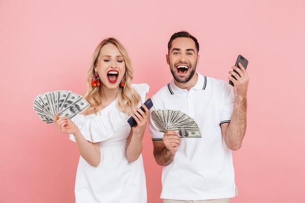 Séduisante jeune couple debout ensemble isolé sur rose, montrant des billets en argent, utilisant un téléphone portable