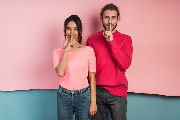 Séduisante jeune couple faisant un geste pour se taire.