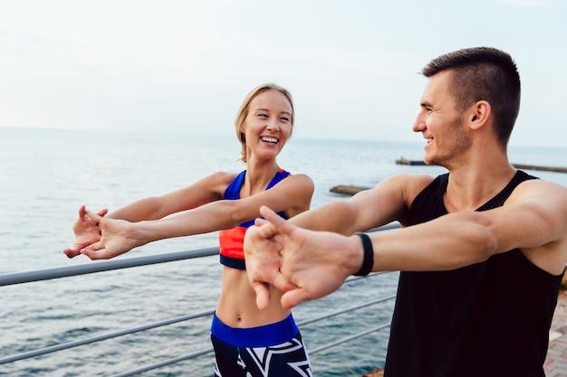Séduisante jeune couple gai faisant des exercices d'étirement des bras tout en travaillant
