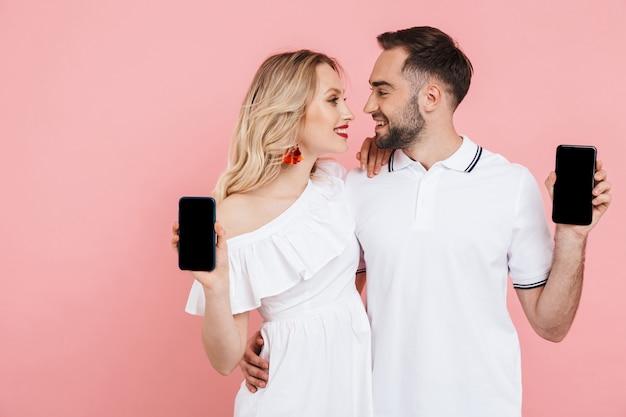 Séduisante jeune couple heureux debout ensemble isolé sur rose, montrant des téléphones portables à écran blanc