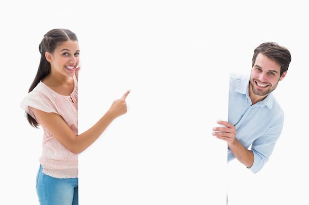Séduisante jeune couple souriant et tenant l'affiche