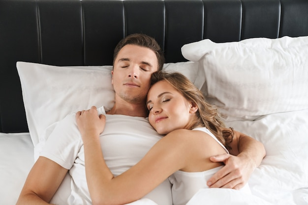 Séduisante jeune couple souriante allongée dans son lit dans la chambre à la maison, embrassant, dormant