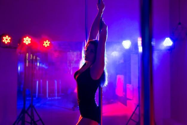 Séduisante jeune danseuse de pôle femme sexy effectue