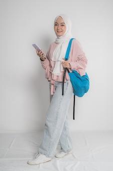 Séduisante jeune étudiant musulman à l'aide de téléphone mobile sur fond blanc isolé