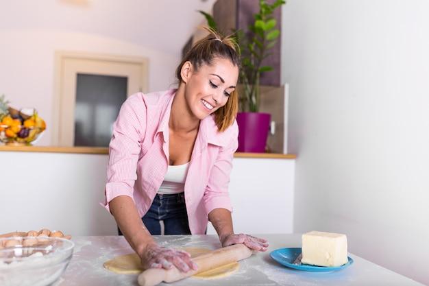 Séduisante jeune femme adulte femme au foyer baker baker tenant la pâte à rouler