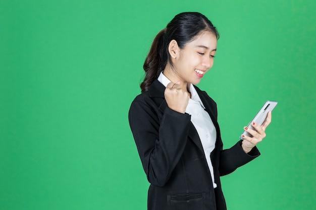 Séduisante jeune femme d'affaires asiatique avec un téléphone intelligent mobile dans les mains