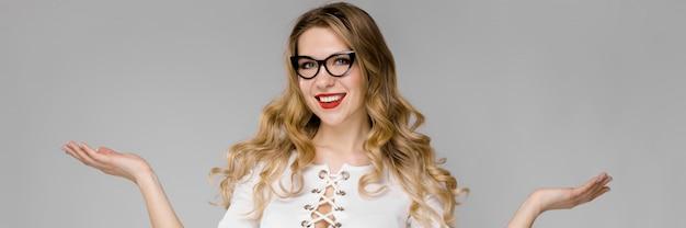 Séduisante jeune femme d'affaires blonde en vêtements noir et blancs, souriant avec les mains ouvertes, debout dans le bureau sur fond gris