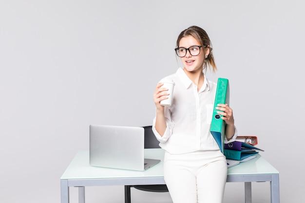 Séduisante jeune femme d'affaires debout près de bureau avec dossier dans le bureau boire du café, isolé sur fond blanc