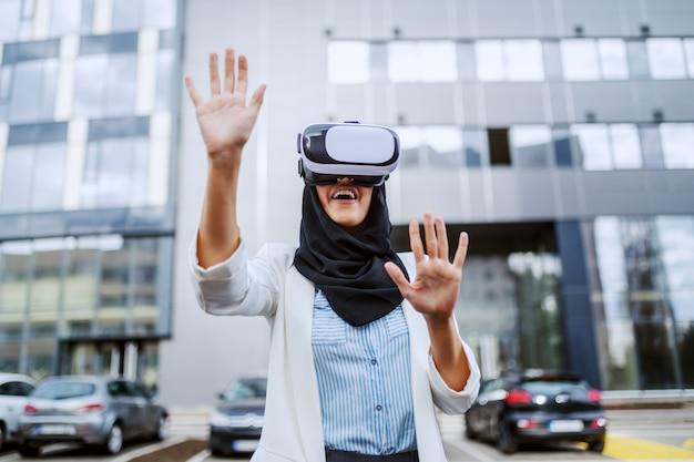 Séduisante jeune femme d'affaires musulmane avec foulard sur la tête à l'aide de lunettes vr pour une présentation virtuelle. génération millénaire.