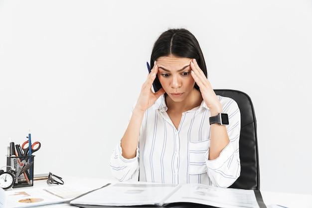 Séduisante jeune femme d'affaires sérieuse assise au bureau isolé sur mur blanc