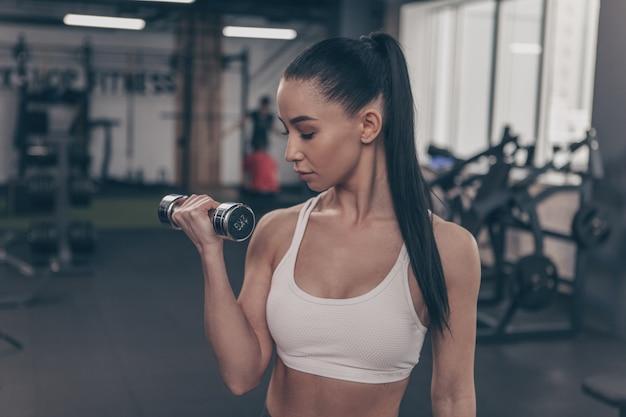 Séduisante jeune femme athlétique, entraînement avec des poids, espace copie