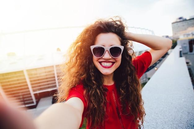 Séduisante jeune femme aux cheveux bouclés prend un selfie, posant et regardant la caméra
