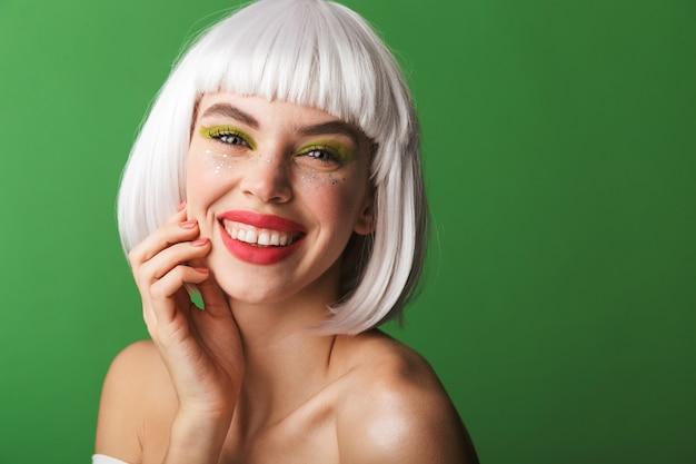 Séduisante jeune femme aux seins nus heureuse portant des cheveux blancs courts debout isolé