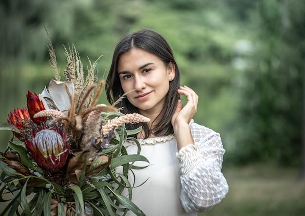 Séduisante jeune femme brune en robe blanche avec un bouquet de fleurs dans la forêt sur fond flou,