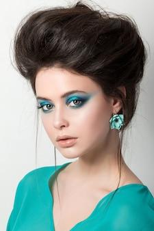 Séduisante jeune femme brunettete dans une robe turquoise portant des oreilles