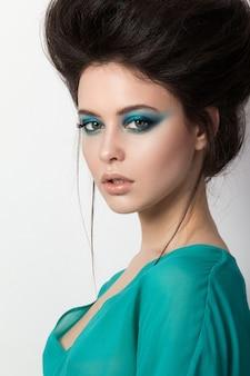 Séduisante jeune femme brunettete dans une robe turquoise