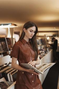 Séduisante jeune femme caucasienne élégante dans une robe brune, lecture de magazine, tourner les pages du livre avec concentré.