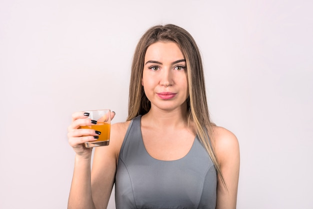 Séduisante jeune femme dans le vêtement de sport avec verre de boisson