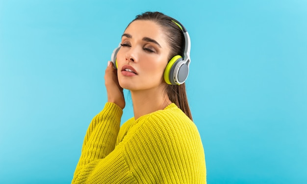 Séduisante jeune femme élégante écoutant de la musique dans des écouteurs sans fil heureux portant chandail tricoté jaune style coloré mode posant isolé sur fond bleu