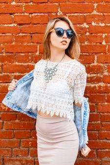 Séduisante jeune femme élégante hipster dans des lunettes de soleil noires dans une veste en jean d'été dans un chemisier en dentelle blanche vintage dans une jupe posant près du mur de briques rouges à l'extérieur