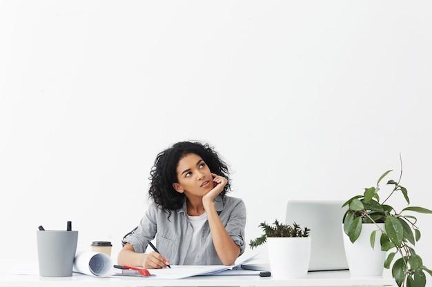 Séduisante jeune femme pensive ingénieur portant chemise grise sur haut blanc à la recherche