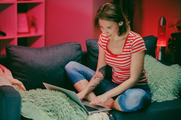 Séduisante jeune femme de race blanche shopping en ligne tout en entrant un numéro de carte de crédit sur l'ordinateur portable à la maison