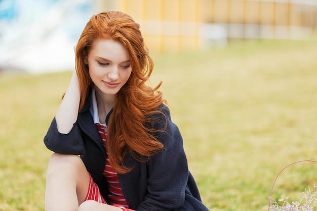 Séduisante jeune femme rousse aux cheveux longs dans le parc
