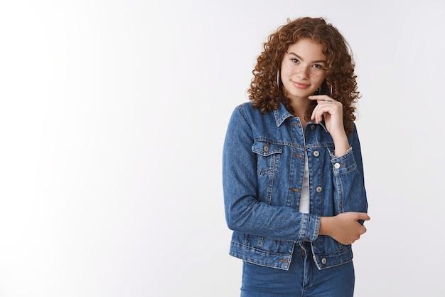 Séduisante jeune femme rousse caucasienne confiante, taches de rousseur, boutons souriant, sournois, sûr de lui, visage tactile réfléchi, avoir une idée de plan intéressant, poitrine de bras croisés, posant sur fond blanc