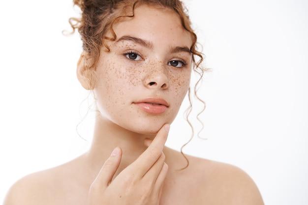 Séduisante jeune femme rousse douce et sensuelle joues nues de taches de rousseur acceptant sa propre peau tactile positive pour le corps appliquant un produit de soin de la peau, aller prendre une douche, salle de bain debout sur fond blanc