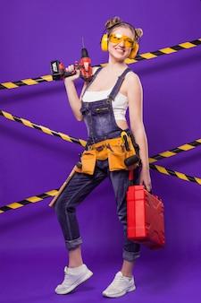 Séduisante jeune fille de constructeur en combinaison de denim et lunettes se tenir avec un tournevis et une boîte à outils