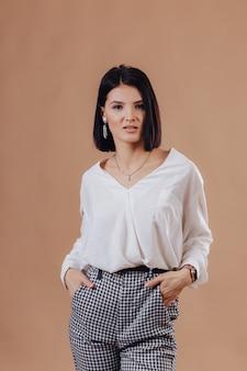 Séduisante jeune fille élégante en tenue d'affaires posant sur le mur de crème. concept de vêtements élégants et sophistiqués.