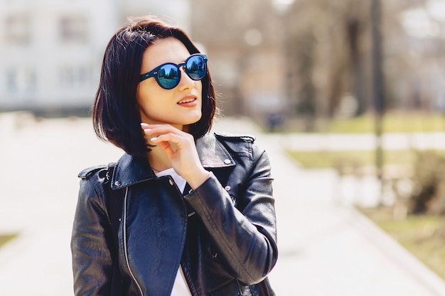 Séduisante jeune fille à lunettes de soleil par journée ensoleillée