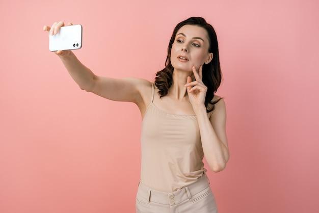 Séduisante, jeune fille posant en prenant une photo de selfie sur téléphone mobile