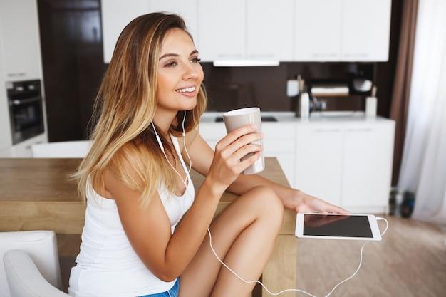 Séduisante jeune fille souriante assise à la cuisine et écouter de la musique.