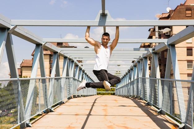 Séduisante jeune homme accroché au plafond du pont