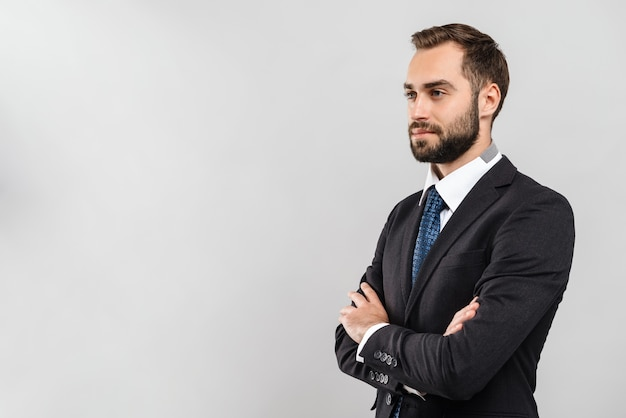 Séduisante jeune homme d'affaires portant un costume debout isolé sur un mur gris, les bras croisés