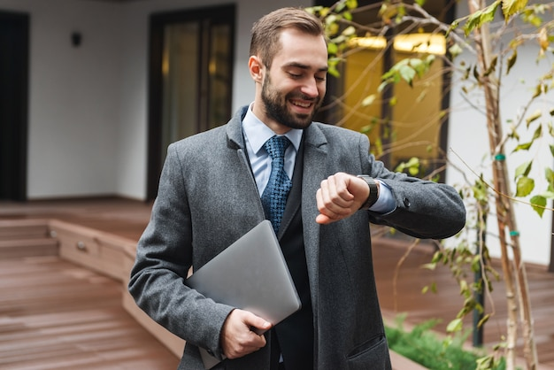 Séduisante jeune homme d'affaires portant costume marchant à l'extérieur, portant un ordinateur portable