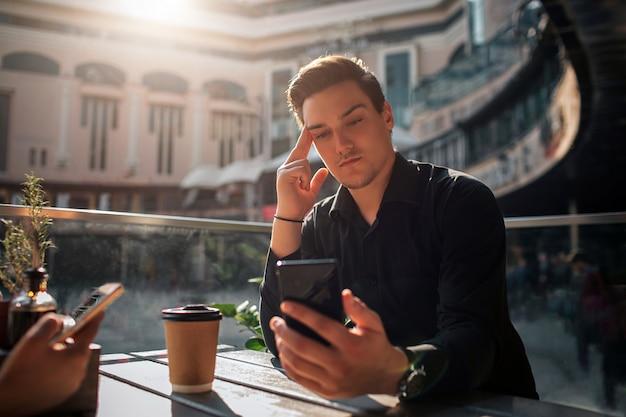 Séduisante jeune homme assis à table et regarde le phon qu'il tient dans la main. guy est concentré. le soleil brille dehors.