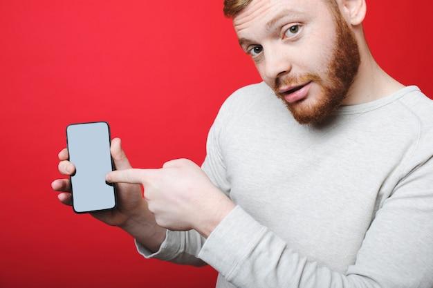 Séduisante jeune homme avec barbe au gingembre regardant la caméra et pointant sur smartphone moderne