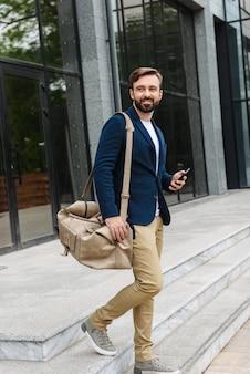 Séduisante jeune homme barbu souriant portant une veste marchant à l'extérieur dans la rue, sac de transport, tenant un téléphone portable