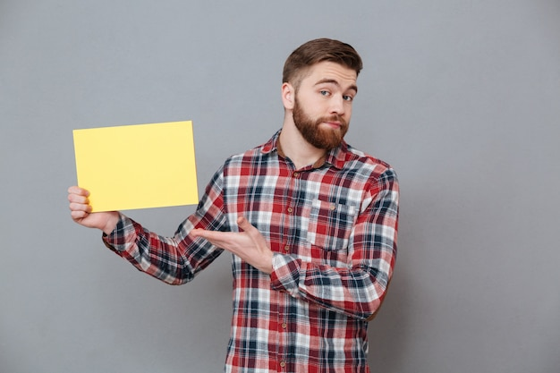 Séduisante jeune homme barbu tenant du papier vierge