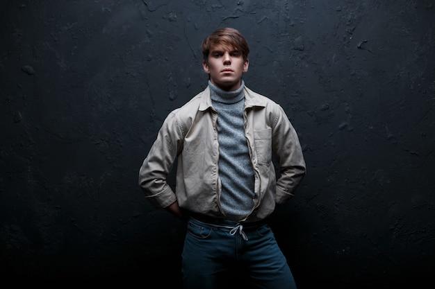 Séduisante jeune homme avec une coiffure à la mode dans une veste élégante blanche en jeans élégant bleu dans des stands de golf vintage gris et se penche sur la caméra dans un studio sombre près d'un mur gris. beau mec