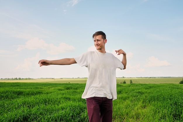 Séduisante jeune homme dans un t-shirt blanc se tenant dans un champ de blé vert jeune, profitant de la nature