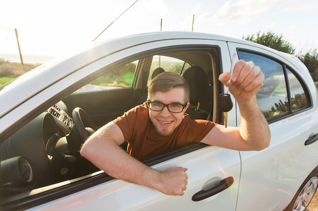Séduisante jeune homme heureux montrant ses nouvelles clés de voiture et riant.
