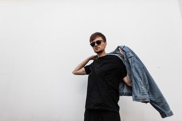 Séduisante jeune homme met une veste en jean
