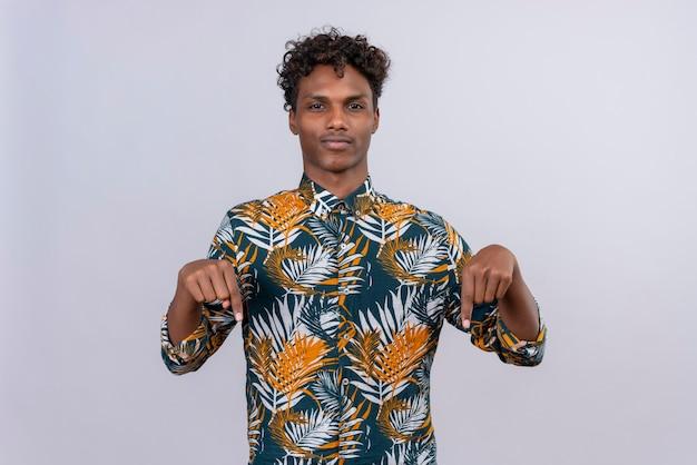 Séduisante jeune homme à la peau sombre aux cheveux bouclés dans les feuilles de chemise imprimée pointe vers le bas avec les deux index
